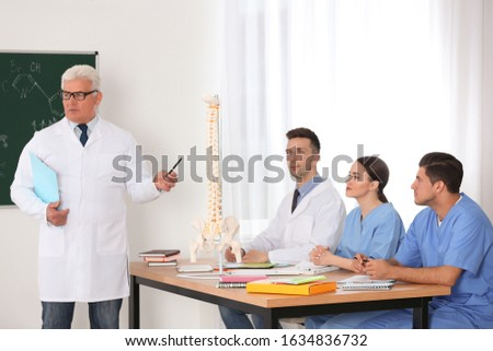 Medical students and professor studying human spine structure in classroom