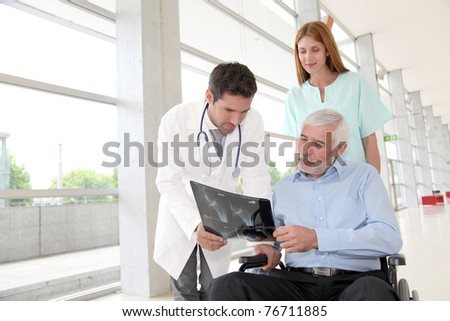 Medical team checking X-ray with patient - stock photo