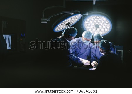Medical team performing surgery. Group of surgeons in hospital operation theater.