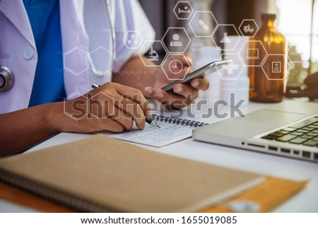 Medical technology concept. Doctor working with mobile phone and stethoscope and digital tablet laptop in modern office at hospital in morning light.