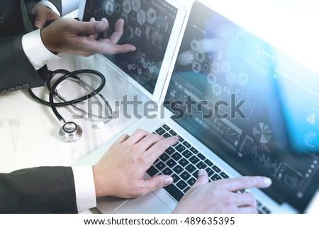 Medical technology network team meeting concept. Doctor hand working smart phone modern digital tablet laptop computer graphics chart interface, sun flare effect photo