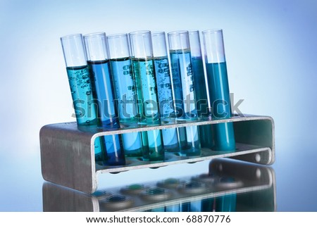 Medical test tubes in stand on blue background