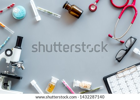 Medical tests on work table of doctor with microscope, cardiogram, test tube on gray background top view copyspace