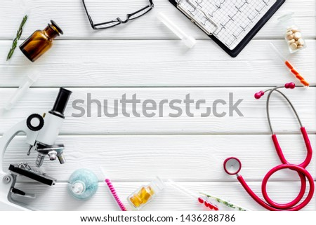 Medical tests on work table of doctor with microscope, cardiogram, test tube on white background top view copyspace