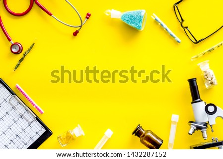 Medical tests on work table of doctor with microscope, cardiogram, test tube on yellow background top view copyspace