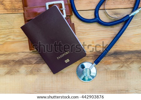 Medical tourism concept. Stethoscope with passport on wooden table. #442903876