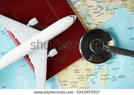 Medical travel concept with stethoscope passport document and airplane on world map background. #1043493907