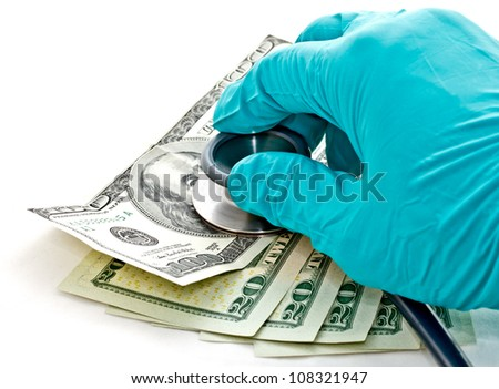 medical treatment and cost concept: doctor's hand hold stethoscope placing on US dollar banknotes