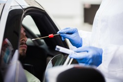 Medical UK NHS worker performing drive-thru COVID-19 test,taking nasal swab specimen sample from male patient through car window,PCR diagnostic for Coronavirus presence,doctor in PPE holding test kit