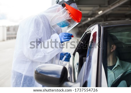 Medical worker in PPE performing nasal & throat swab on person in vehicle through car window,COVID-19 mobile testing centre,drive through facility parking lot,specimen collection and rt-PCR diagnostic