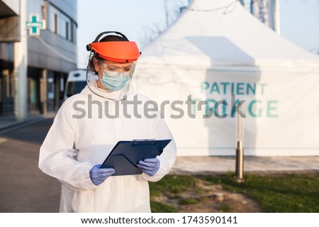 Medical worker wearing PPE protective white suit,face shield mask,holding clipboard patient health check up form,standing in front of clinic hospital,triage tent for COVID-19 UK point of care testing Foto stock ©