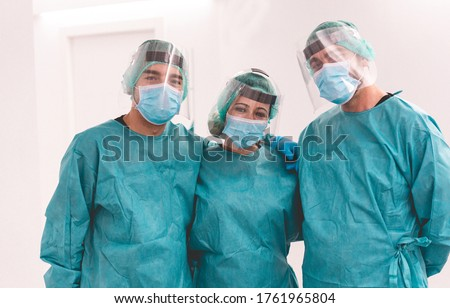 Medical workers inside hospital corridor during coronavirus pandemic outbreak - Doctor and nurse at work on Covid-19 crisis period - Health care concept - Main focus on center woman face
