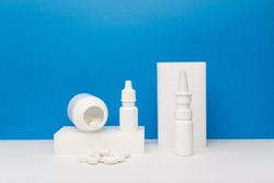 Medication bottle with spilled pills on podium, nose spray and eye drops against blue background