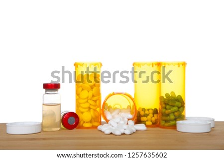 Medication bottles standing and spilling on a wood table with injectable vials laying next to them. Depicting multiple medications, overwhelming, addiction, pain management. Isolated on white. #1257635602