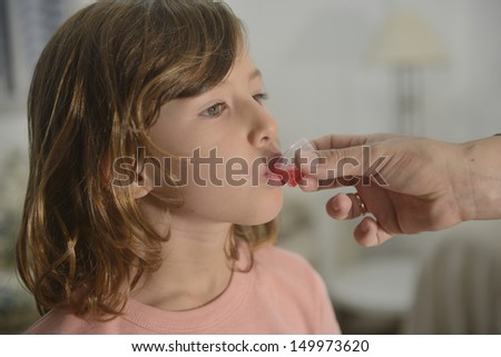 Medication: little girl taking cough syrup