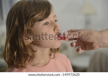 Medication: little girl taking cough syrup