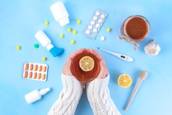 Medications, pills, thermometer, traditional medicine for treating colds, flu, heat on a blue background. Maintenance of immunity. Seasonal diseases. Top view. Medicine flat lay
