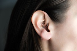 medicinal earring in ear to treat headaches