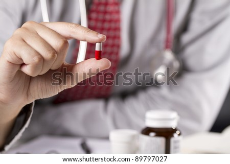 medicine, a doctor showing red and white capsule pill.