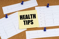 Medicine and health concept. Attached to the board are cardiogram clippings and a sticker with the inscription - HEALTH TIPS