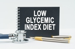 Medicine and health concept. On a white background lies a stethoscope, a pen and a black notebook with the inscription - LOW GLYCEMIC INDEX DIET