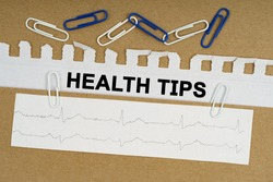 Medicine and health concept. On the table lies a cardiogram, paper clips and paper with the inscription - HEALTH TIPS