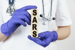 Medicine and health concept. The doctor holds cubes in his hands on which it is written - SARS. ATYPICAL PNEUMONIA