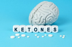 Medicine and health. Cubes lie on the table among the pills and imitation of the brain. The text on the dice - KETONES