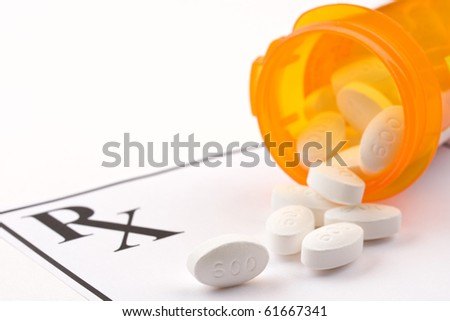 Medicine bottle and pills laying on prescription.