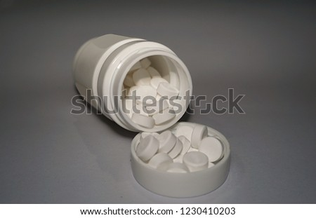 Medicine bottle with pills on the lid of medicine bottle, treat people from illness. Good for health of sick. #1230410203