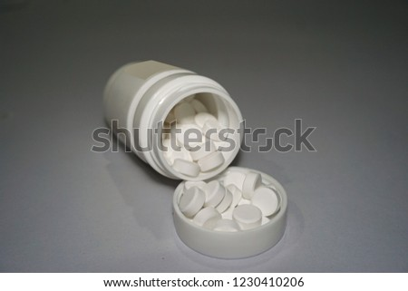 Medicine bottle with pills on the lid of medicine bottle, treat people from illness. Good for health of sick. #1230410206