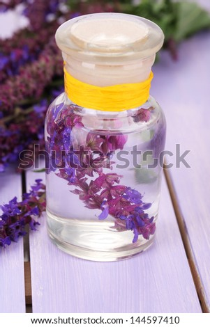 Medicine bottle with salvia flowers on purple wooden background