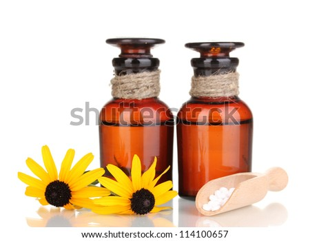 medicine bottles with tablets and flowers isolated on white
