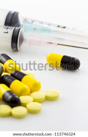 Medicine capsule and tablet with syringe, closeup and selective focus