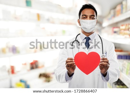 medicine, cardiology and healthcare concept - indian male doctor cardiologist or pharmacist wearing face protective medical mask with red heart shape and stethoscope over drugstore background