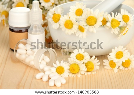 Medicine chamomile flowers on wooden table