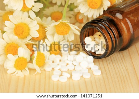 Medicine chamomile flowers on wooden table - stock photo