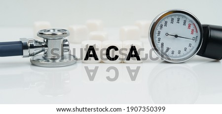 Medicine concept. On a reflective white surface lies a stethoscope and cubes with the inscription - ACA Imagine de stoc ©