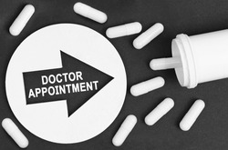Medicine concept. Pills on a black background. They are indicated by a circle with an arrow, inside which it is written - DOCTOR APPOINTMENT