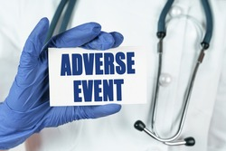 Medicine concept. The doctor holds a business card that says - ADVERSE EVENT