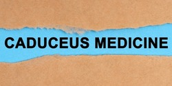 Medicine concept. The paper is ripped in the middle. Inside on a blue background it is written - Caduceus Medicine