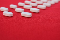 Medicine concept. White tablets are laid out in a line on a red background. Pill red frame isolated. Medicines or drugs arranged in a rectangular frame on light blue gradient background,medicine.