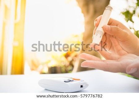 Medicine, Diabetes, Glycemia, Health care and people concept - close up of female using lancelet on  finger to checking blood sugar level by Glucose meter