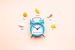 medicine drugs daily and weekly schedule concept. assorted drugs near alarm clock. above view. drug medication reminder conceptual. pink background.