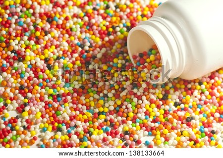 medicine for children - a colorful candy / sweet spilled out of a medical pill box / can / tube
