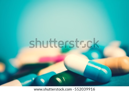 Medicine green and yellow pills or capsules on blue background with copy space. Drug prescription for treatment medication. Pharmaceutical medicament, cure in container for health. Antibiotic