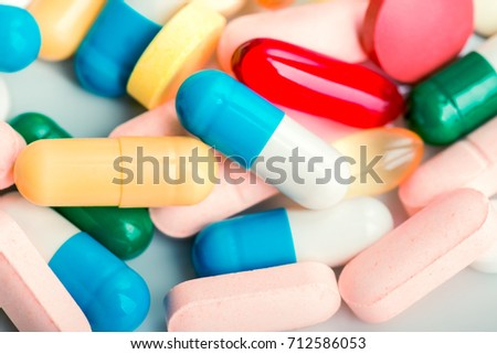 Medicine green and yellow pills or capsules on white background. Drug prescription for treatment medication. Pharmaceutical medicament, cure in container for health. Antibiotic