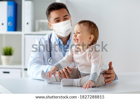 medicine, healtcare, pediatry and people concept - happy doctor or pediatrician wearing face protective mask for protection from virus disease with baby on medical exam at clinic Zdjęcia stock ©