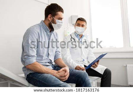 medicine, healthcare and pandemic concept - male doctor wearing face protective medical mask for protection from virus disease with clipboard and young man patient meeting at hospital Foto stock ©