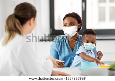 medicine, healthcare and pediatry concept - caucasian doctor giving prescription to african american mother wearing protective medical mask for protection from virus disease with baby son at clinic